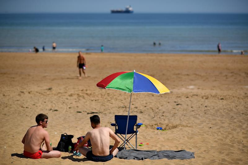 """People enjoy the sunshine on the beach and in the sea at Botany Bay, near Margate, south east England on May 26, 2020, after some lockdown restrictions put in place to slow the spread of COVID-19 were partially eased earlier this month. - Britain's number of deaths """"involving"""" the coronavirus has risen to 46,000, substantially higher than the 36,914 fatalities officially reported so far, according to a statistical update released Tuesday. The daily death tolls released in Britain only include fatalities that have been confirmed by a positive test. (Photo by Ben STANSALL / AFP) (Photo by BEN STANSALL/AFP via Getty Images)"""
