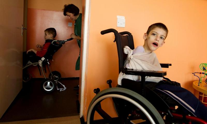 A nurse pushes a child on a wheelchair at an orphanage for mentally disabled children near Vesnova, Belarus, in 2013