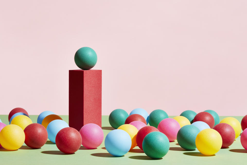 A green sphere stands on top of a pedestal surrounded by a crowd of multicoloured spheres