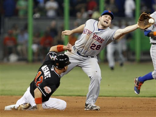 Miami Marlins' Omar Infante (12) steals second base as New York Mets second baseman Daniel Murphy (28) waits for the throw during the first inning of a baseball game on Friday, May 11, 2012, in Miami. (AP Photo/Wilfredo Lee)