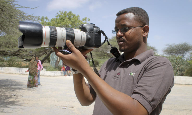 In this photo taken Friday, Jan. 18, 2013, Somali journalist Mohamed Mohamud holds his camera in the Medina hospital compound in Mogadishu, Somalia. A Somali journalist says colleague Mohamed Mohamud, who was also known as Tima'ade and reported for the private U.K.-based Universal TV, has died of his wounds in hospital Saturday night Oct. 26, 2013 after being shot six times by gunmen on Tuesday, Oct. 22, 2013, bringing to seven the number of Somali journalists murdered this year, with at least 18 killed last year. (AP Photo/Farah Abdi Warsameh)