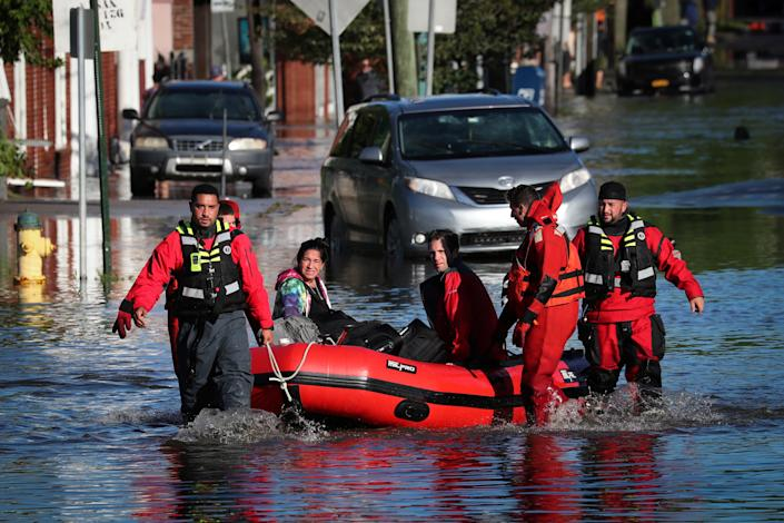 First responders in Mamaroneck, N.Y., pull residents in a boat as they rescue people trapped by floodwaters on Thursday.