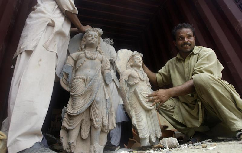 In this Friday, July 6, 2012 photo, Pakistani workers unload ancient Buddhist sculptures from a container seized by police Friday, that smugglers were attempting to spirit out of the country, in Karachi, Pakistan. Pakistani officials say police have seized many sculptures of Buddha and other related religious figures worth millions of dollars that experts indicated could be over 2,000 years old. (AP Photo/Shakil Adil)
