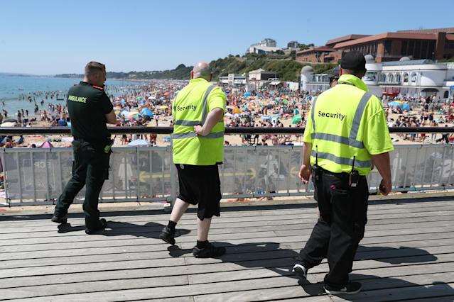A member of the Ambulance Service walks with two security staff along Bournemouth Pier (Picture: Getty)