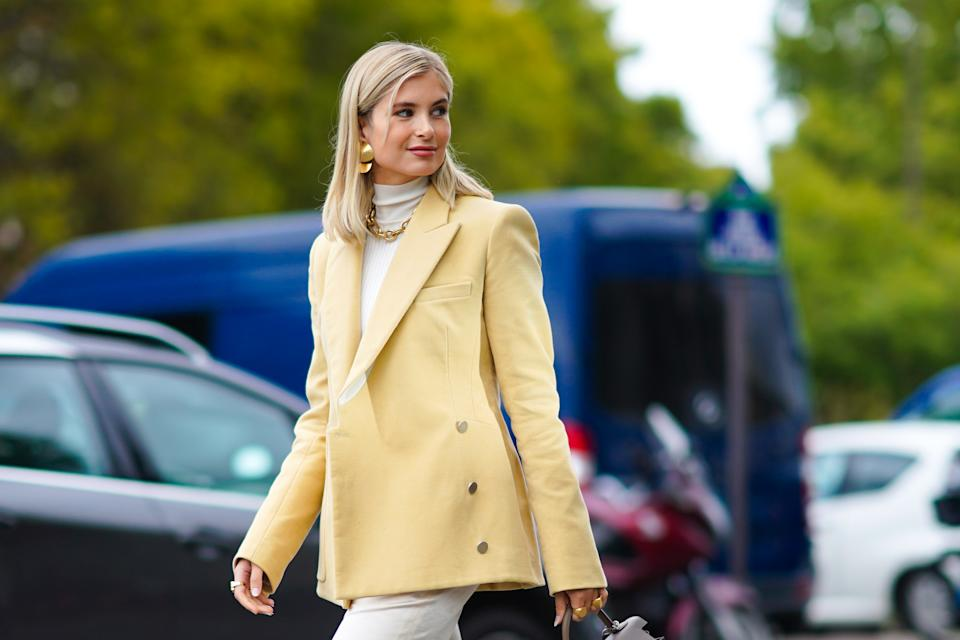 PARIS, FRANCE - OCTOBER 03: Xenia Adonts wears golden earrings, a white turtleneck pullover, a pale yellow oversized blazer jacket, a brown Hermes bag, a golden chain necklace, outside Hermes, during Paris Fashion Week - Womenswear Spring Summer 2021 on October 03, 2020 in Paris, France. (Photo by Edward Berthelot/Getty Images)