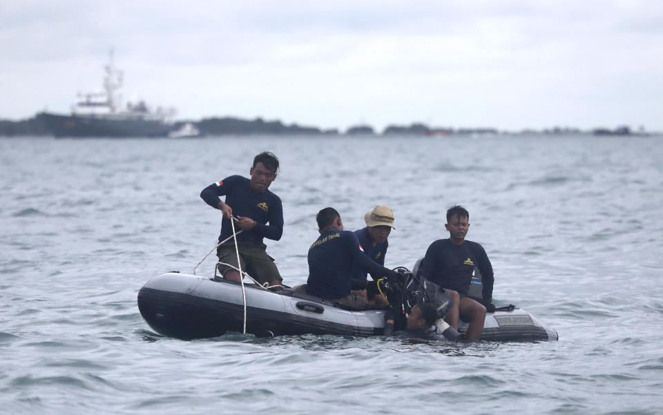 Indonesian Navy divers continue their search for wreckage of the crashed Sriwijaya Air passenger jet in the Java Sea, near Jakarta, Indonesia, Tuesday, Jan. 12, 2021. Indonesian navy divers were searching through plane debris and seabed mud Tuesday looking for the black boxes of a Sriwijaya Air jet that nosedived into the Java Sea over the weekend with 62 people aboard. (AP Photo/Tatan Syuflana)