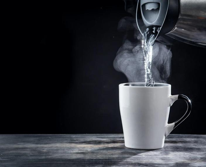 Pouring hot water into into a cup on a black background