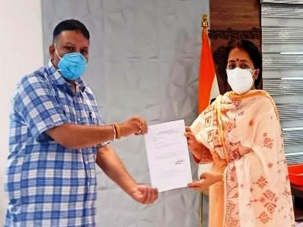 Udhampur Deputy Commissioner Indu Chib (right) handing over to the disbursal paper to Assistant Labour Commissioner Pradyot Gupta.