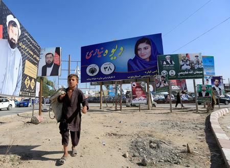 Election posters of parliamentary candidates are installed on a street while a boy walks past in Jalalabad, Afghanistan October 6, 2018. REUTERS/Parwiz