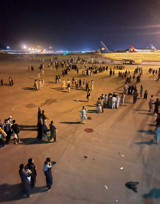 An undated amateur picture obtained by Reuters on August 19, 2021 shows people walking on the tarmac of the airport in Kabul, Afghanistan.    Handout via REUTERS    NO RESALES. NO ARCHIVES (Photo: HANDOUT via via REUTERS)