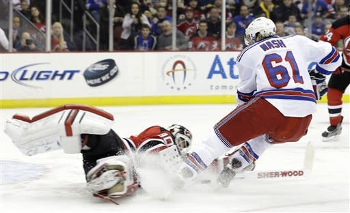 New Jersey Devils goalie Martin Brodeur, left, makes a save on a shot by New York Rangers left wing Rick Nash (61) during the first period of an NHL hockey game, Tuesday, Feb. 5, 2013, in Newark, N.J. (AP Photo/Julio Cortez)