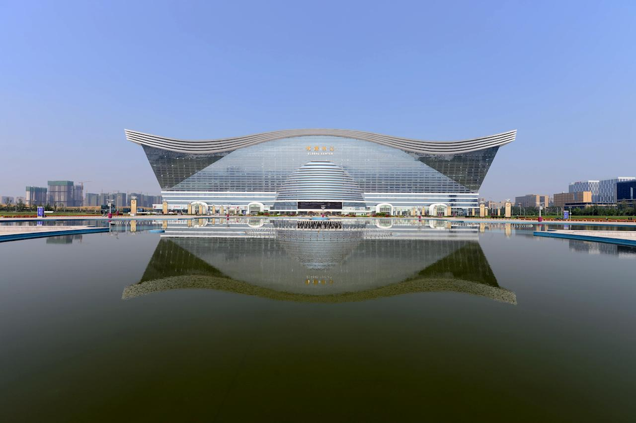 "The ""New Century Global Centre"" building is seen behind an artificial lake in Chengdu, in southwest China's Sichuan province on June 6, 2013. The center, claimed by Chinese officials as ""the world's largest standalone structure"", is going to be opened to the public on June 28. The 100m high ""New Century Global Centre"" is a symbol of the spread of China's boom: 500m long and 400m wide, with 1.7 million square metres of floor space - big enough to hold 20 Sydney Opera Houses, according to local authorities.  CHINA OUT     AFP PHOTO"