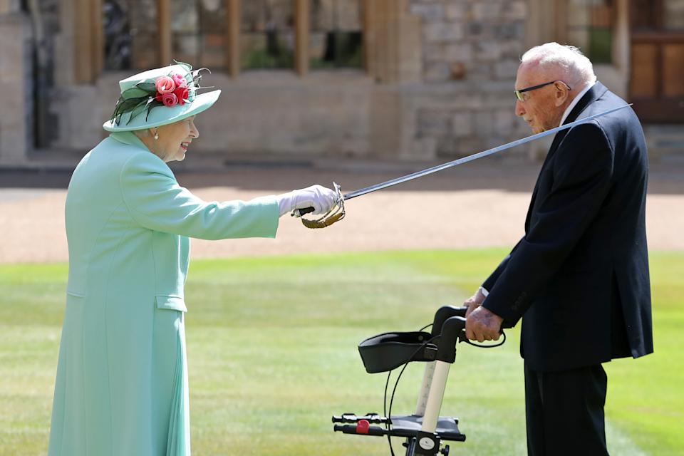 Captain Sir Thomas Moore receives his knighthood from Queen Elizabeth II during a ceremony at Windsor Castle.