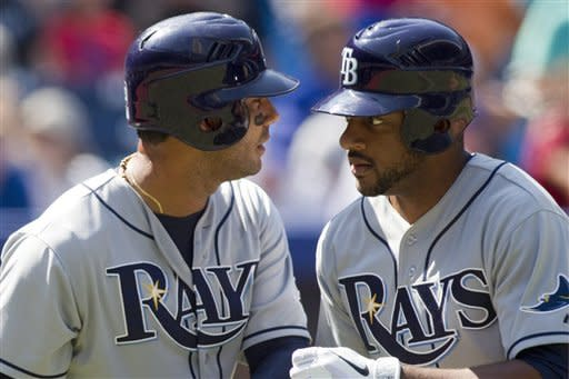 Tampa Bay Rays' Ben Francisco, right, is congratulated by teammate Carlos Pena after hitting a home run off Toronto Blue Jays pitcher Ricky Romero during the second inning of baseball game action in Toronto, Sunday, Sept. 2 , 2012. (AP Photo/The Canadian Press, Chris Young)