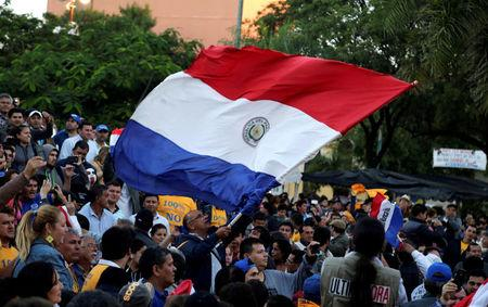 People wave a Paraguayan flag to celebrate the rejection of a proposed amendment to allow presidential second terms, in front of the Paraguayan Congress, in Asuncion, Paraguay April 26, 2017. REUTERS/Jorge Adorno