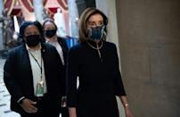 House Speaker Nancy Pelosi, who is known for her suits' bright colors, opted for the same dark outfit she wore for President Donald Trump's first impeachment