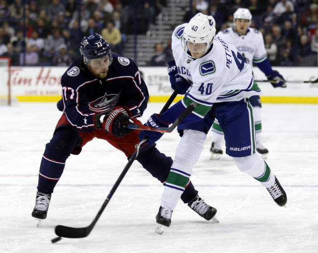 Vancouver Canucks forward Elias Pettersson, right, of Sweden, passes against Columbus Blue Jackets forward Josh Anderson during the first period of an NHL hockey game in Columbus, Ohio, Tuesday, Dec. 11, 2018. (AP Photo/Paul Vernon)