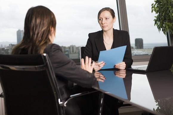 Two professionally dressed women seated at a conference table and talking to each other
