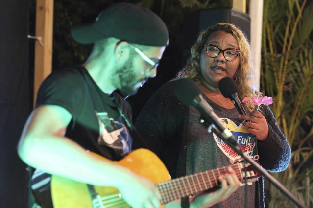 """In this Jan. 12, 2019 photo, Venezuelan singer Reymar Perdomo performs with fellow Venezuelan and guitarist Omar Rumbos at a fair on the beach of San Bartolo, Peru. Perdomo's song """"Me Fui"""" is her retelling of how she left Venezuela reluctantly with her """"head full of doubts,"""" pushed by her mother, who insisted there was no other way for her to make something of her life. (AP Photo/Martin Mejia)"""