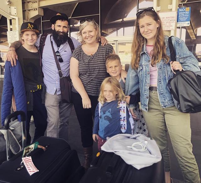 Charles MacDonald, second from left, stands next to his wife, Janelle Hanchette, surrounded by their four children — from left, Rocket, George and Ava, and, in front, Arlo — at the San Francisco International Airport on their way to the Netherlands in July. (Photo: courtesy of the family)