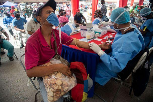 PHOTO: A health worker takes a blood sample for a quick COVID-19 test from man who works selling cookies at the Coche food market in Caracas, Venezuela, June 23, 2020. (Ariana Cubillos/AP)