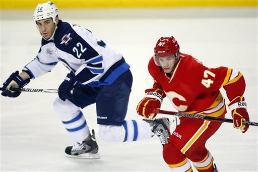 Winnipeg Jets' Chris Thorburn, left, outpaces Calgary Flames' Sven Baertschi, from Switzerland, during first-period NHL hockey game action in Calgary, Alberta, Friday, March 9, 2012. (AP Photo/The Canadian Press, Jeff McIntosh)
