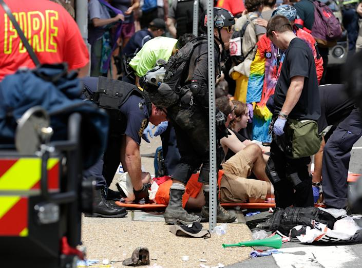 """<p>Rescue workers assist people who were injured when a car drove through a group of counter protestors at the """"Unite the Right"""" rally Charlottesville, Va., Aug. 12, 2017. (Photo: Joshua Roberts/Reuters) </p>"""