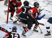 Japan goalie Nana Fujimoto (1) loses track of the puck as teammate Shiori Koike (2) tries to hold off Hilary Knight, right, of the United States, during first-period quarterfinal IIHF women's world championship hockey game action in Calgary, Alberta, Saturday, Aug. 28, 2021. (Jeff McIntosh/The Canadian Press via AP)