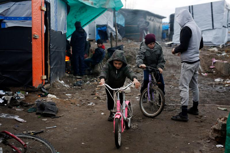 Afghan children ride their bicycles in a makeshift migrants camp near Calais, France, in 2016. (Photo: ASSOCIATED PRESS)