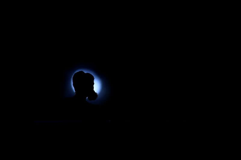 FILE PHOTO: An anti-extradition bill protester is silhouetted in front of the moon, during the march to demand democracy and political reforms, in Hong Kong