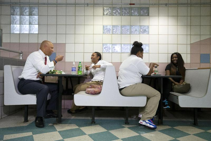 Superintendent William Hite, left, eats with students during the first day of school at South Philadelphia High School, Monday, Sept. 9, 2013, in Philadelphia. About 190,000 students are going back to class Monday in Philadelphia, where parents say severe staffing cuts have created an aura of uncertainty around the new academic year. Officials contend the school district is prepared despite the major budget reductions. (AP Photo/Matt Rourke)