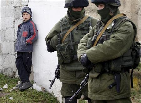 A boy looks at uniformed men, believed to be Russian servicemen, near a Ukrainian military base in the village of Perevalnoye, outside Simferopol, March 6, 2014. REUTERS/Vasily Fedosenko