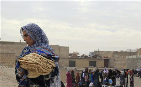 File photo shows a woman holding bread in Minbij city in the east countryside of Aleppo