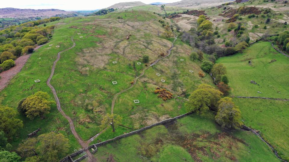Hillside in the Lake District with crates for saplings scattered across the landscape (National Trust/PA)