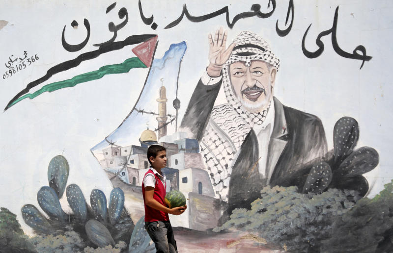 """A Palestinian youth walks next to a mural depicting late Palestinian leader Yasser Arafat, in the northern West Bank village of Kabatyeh, Wednesday, July 4, 2012. Arabic text quotes a famous idiom meaning """"We are holding to our promise."""" (AP Photo/Mohammed Ballas)"""