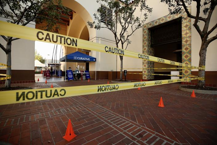Caution tape in front of a blue tent with the word Curative on it