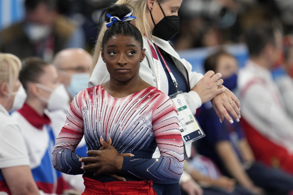 Simone Biles, of the United States, looks at the score after her performance on the balance beam during the artistic gymnastics women's apparatus final at the 2020 Summer Olympics, Tuesday, Aug. 3, 2021, in Tokyo, Japan. (AP Photo/Natacha Pisarenko)