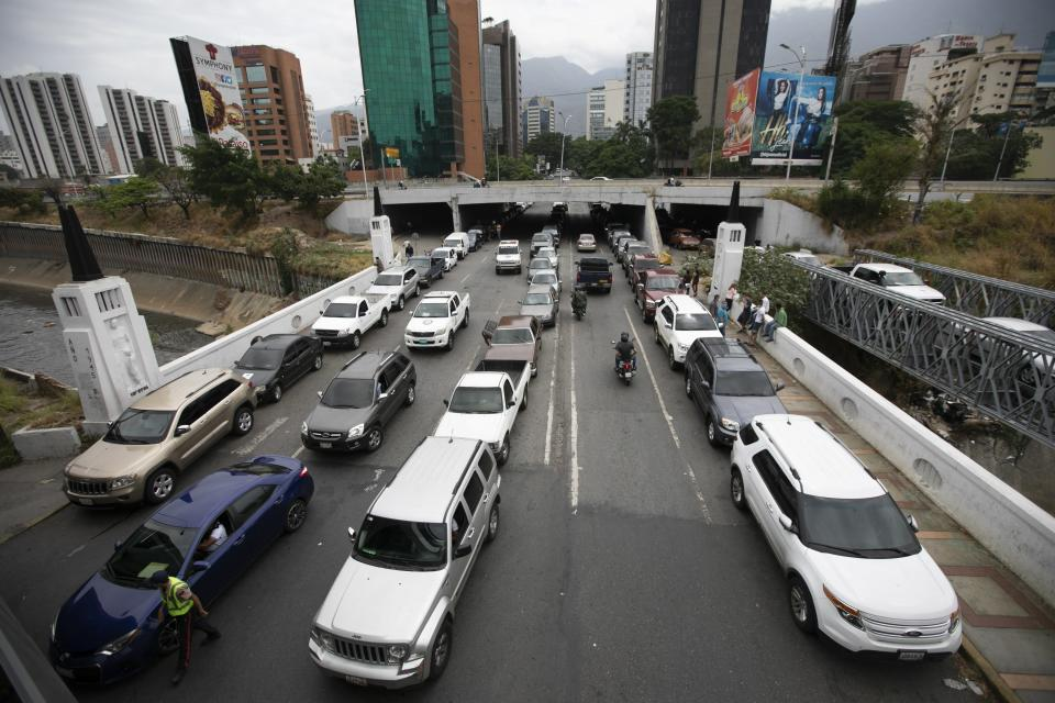 FILE - In this May 29, 2020 file photo, vehicles line up near a gas station to fill their tanks amid a fuel crunch in Caracas, Venezuela. Market research firm IHS Markit forecast in August 2020 that Venezuela could soon be producing almost zero barrels of oil despite sitting atop the world's largest reserves. (AP Photo/Ariana Cubillos, File)