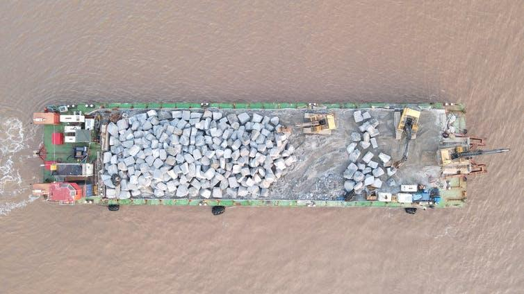 An aerial view of a barge carrying rocks