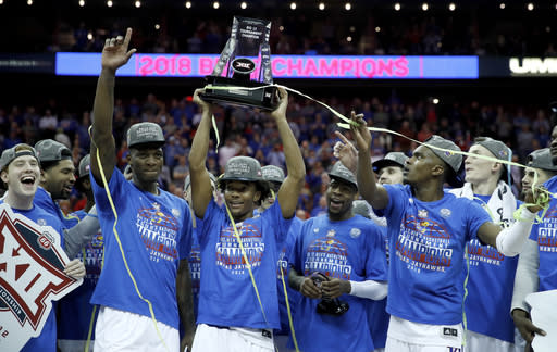 Kansas players celebrate after winning the NCAA college basketball championship game against West Virginia in the Big 12 men's tournament Saturday, March 10, 2018, in Kansas City, Mo. Kansas won 81-70. (AP Photo/Charlie Riedel)