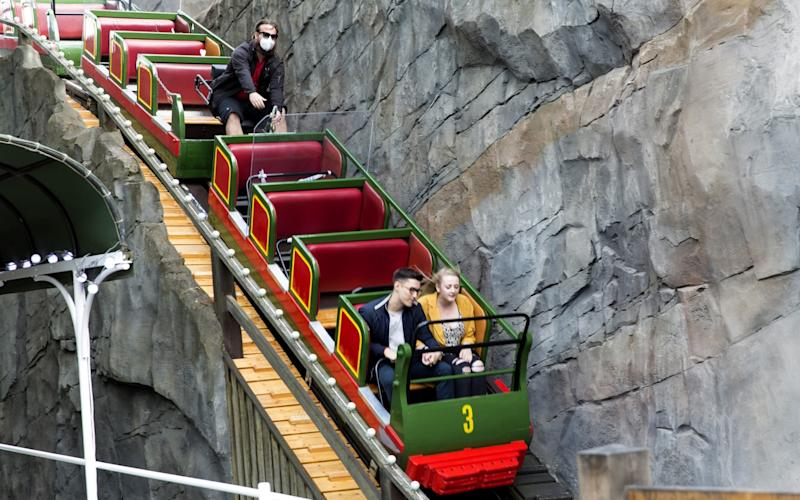 Guests sit on a roller coaster at Tivoli - GETTY IMAGES