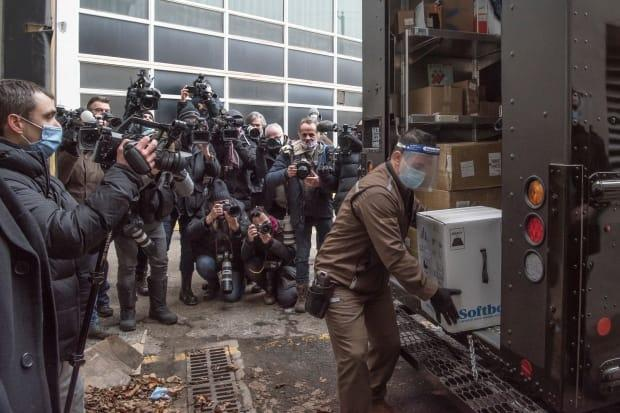 A box of Pfizer/BioNTEch COVID-19 vaccine is taken from a UPS truck past news photographers to the Maimonides long-term care home in Montreal on December 14, 2020.