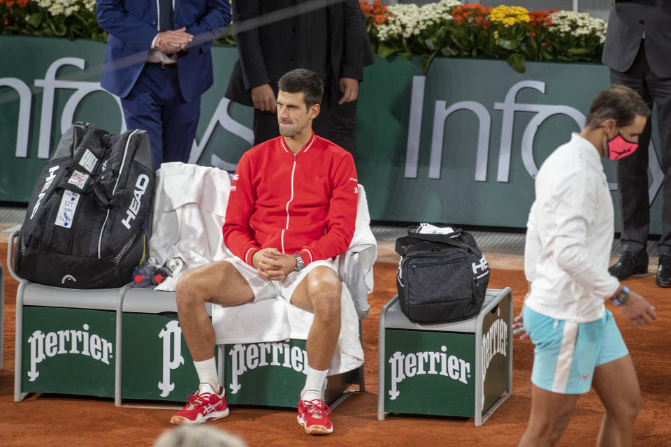 PARIS, FRANCE October 11. Novak Djokovic of Serbia reflects on his loss against Rafael Nadal of Spain who heads back to his seat after an on court interview after the Men's Singles Final on Court Philippe-Chatrier during the French Open Tennis Tournament at Roland Garros on October 11th 2020 in Paris, France. (Photo by Tim Clayton/Corbis via Getty Images)