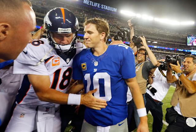 Quarterbacks Peyton Manning (L) and Eli Manning have a brief second of family time after a 2013 game between the Giants and Broncos. (Getty Images)