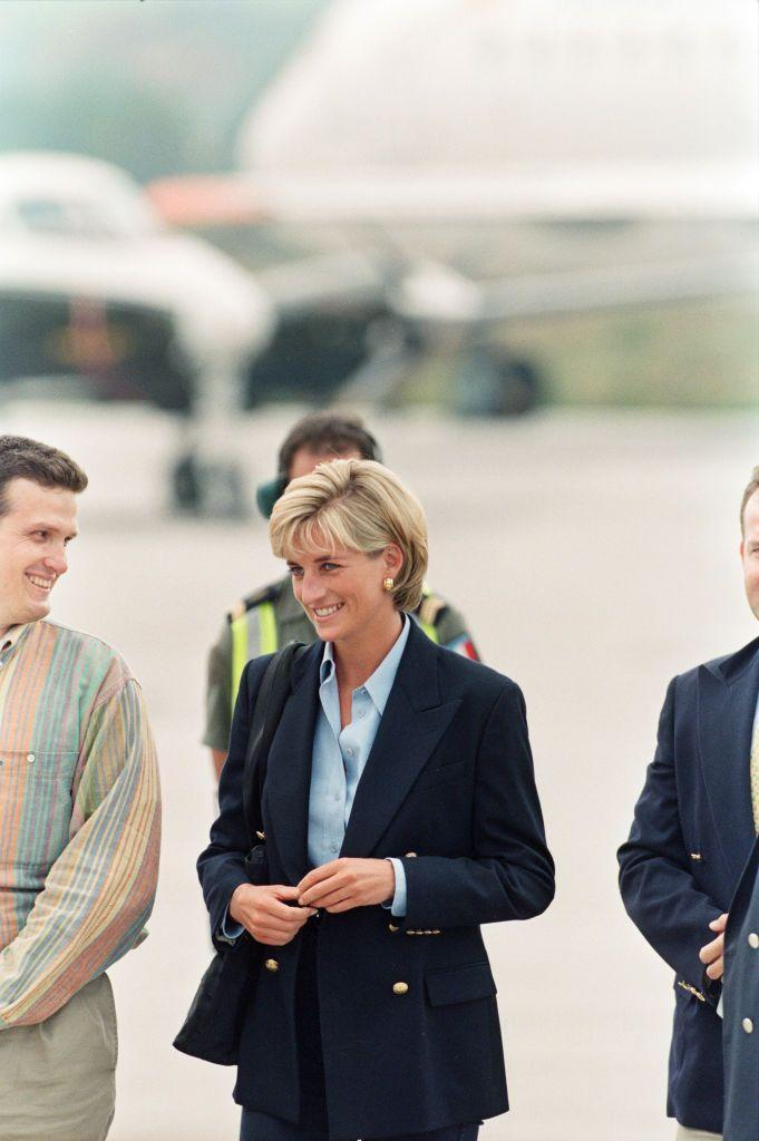 <p>In August 1997, Diana wore a classic navy blazer with statement gold buttons while arriving at Sarajevo airport on a trip to raise awareness on land mines.</p>