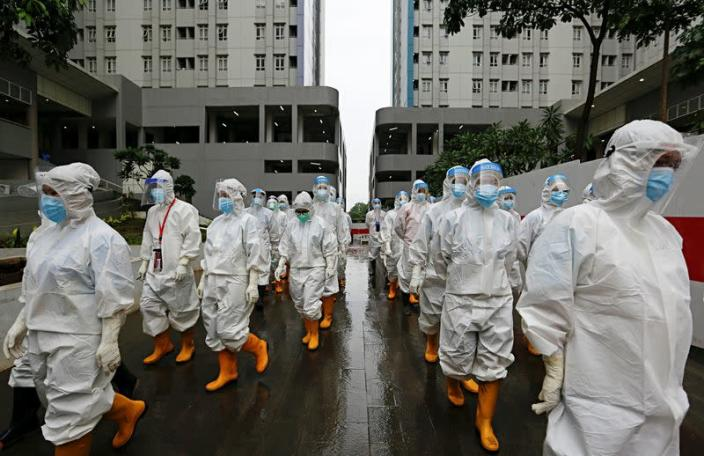 Healthcare workers prepare to treat patients at the emergency COVID-19 hospital in Athletes Village, Jakarta
