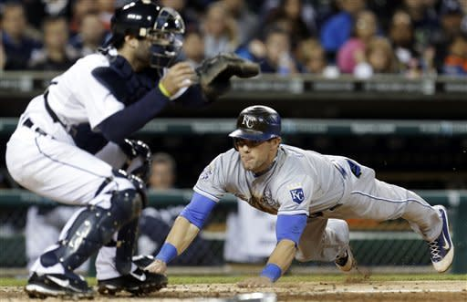 Kansas City Royals left fielder Alex Gordon dives safely into home plate to score on an RBI single by Billy Butler as Detroit Tigers catcher Alex Avila waits for the throw in the third inning of a baseball game in Detroit, Wednesday, Sept. 26, 2012. (AP Photo/Paul Sancya)