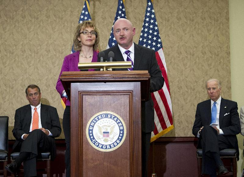 "Former Arizona Rep. Gabrielle Giffords listens as her husband, retired astronaut Mark Kelly speaks on Capitol Hill, in Washington, Tuesday, April 16, 2013, during a ceremony to honor Gabriel ""Gabe"" Zimmerman. Zimmerman was Giffords' outreach director until he was killed in the January 2011 shooting rampage in Tucson where Giffords was wounded. House Speaker John Boehner of Ohio is at left, Vice President Joe Biden is at right. (AP Photo/Jose Luis Magana)"