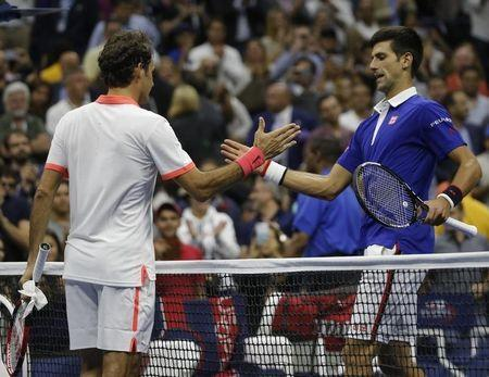 Novak Djokovic of Serbia (R) shakes hands with Roger Federer of Switzerland after Djokovic won their men's singles final match at the U.S. Open Championships tennis tournament in New York, September 13, 2015. REUTERS/Mike Segar