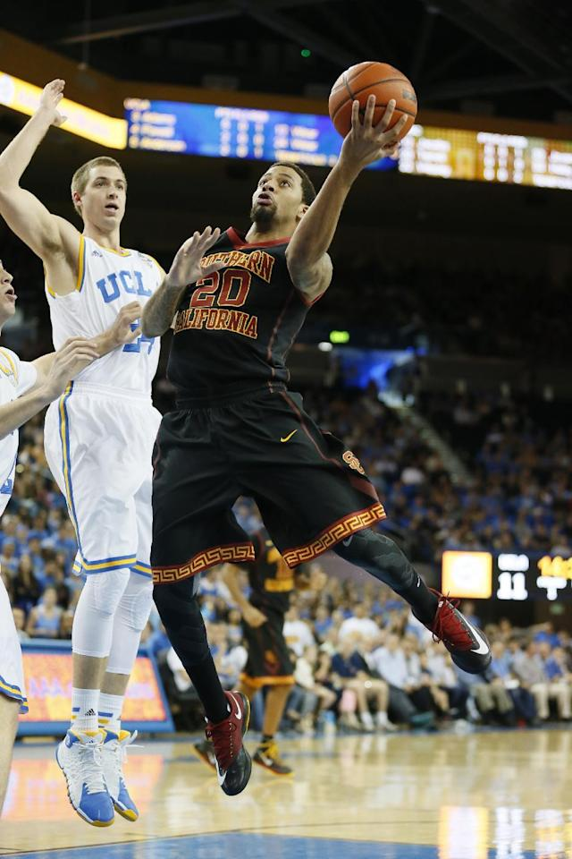 Southern California's J.T. Terrell, right, goes to the basket in front of UCLA's Travis Wear, left, during the first half of an NCAA college basketball game on Sunday, Jan. 5, 2014, in Los Angeles. (AP Photo/Danny Moloshok)